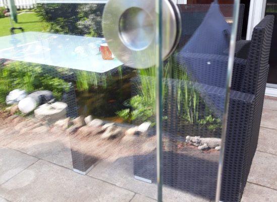 Terrassendach/ Kaltwintergarten mit rahmenlosen Schiebeelementen