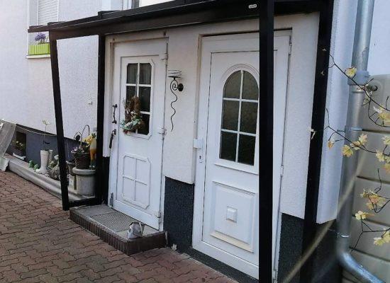 Vordach, mit Milchglas-Eindeckung, über 2 Haustüren nebeneinander.