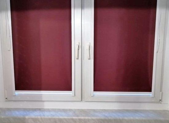 Verdunkelung mit roten Innenrollos in einer Mietwohnung