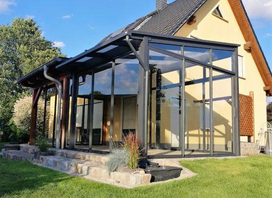 Freistehender Glaspavillion neben Holzdach