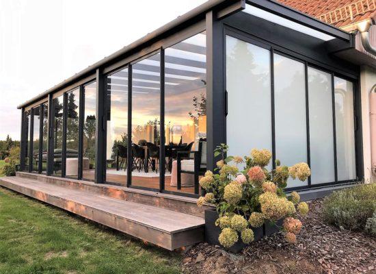 Sommergarten mit seitlichem Dachüberstand und Sichtschutz-Glas im Giebel und gerahmte Schiebeanlagen in der Front