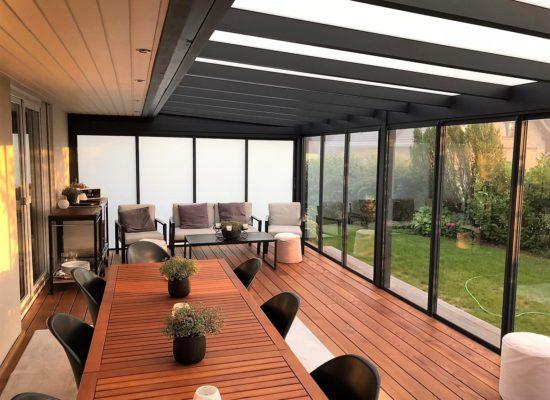 Holzterrasse mit Treppe von Außen und Schiebetüren im Terrassendach
