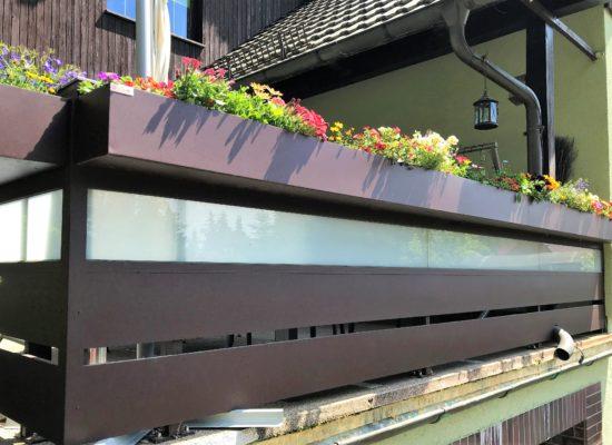 Maßgefertigtes ALU-Geländer mit Glaselementen und Blumenkästen.